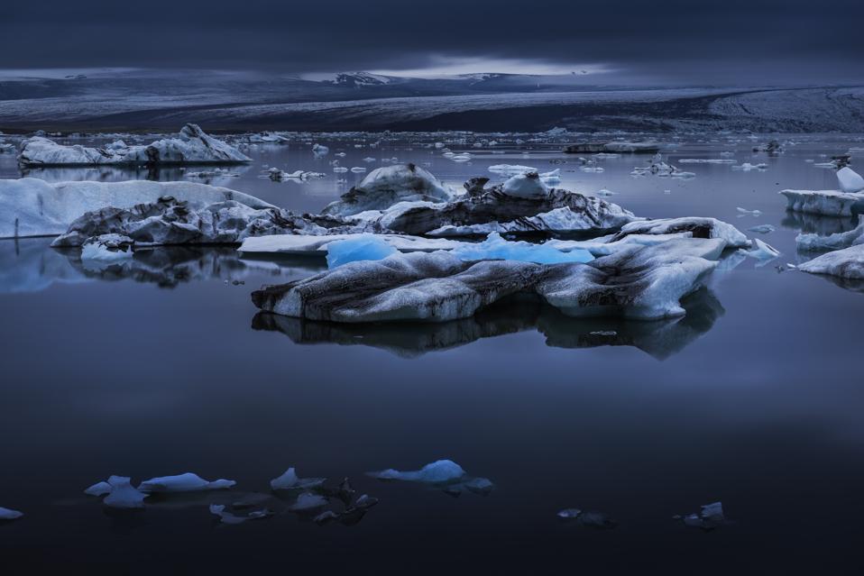 Icebergs floating on lake at evening