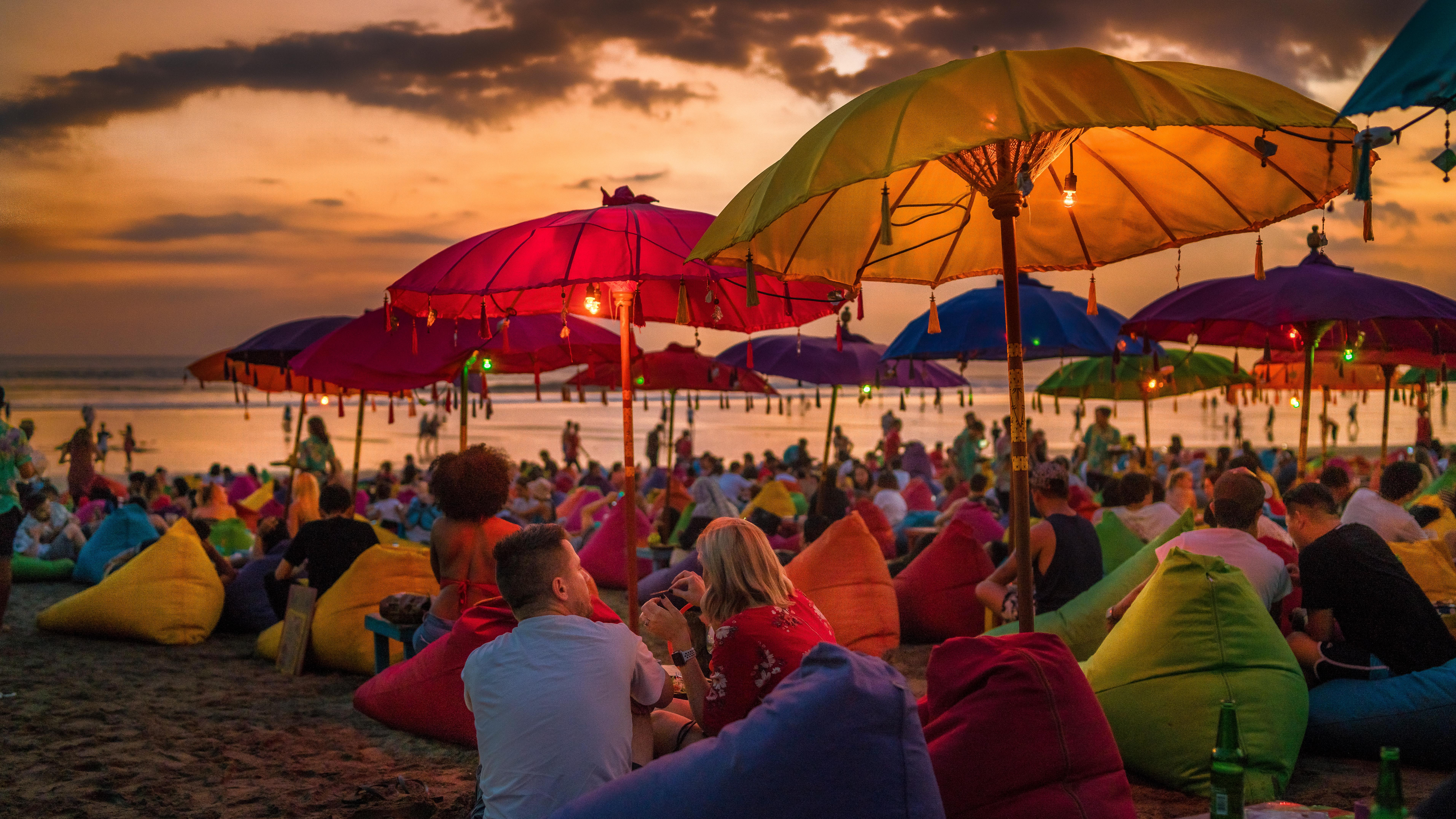 Crowded tourists relaxing on the beach at dusk in Bali, Indonesia