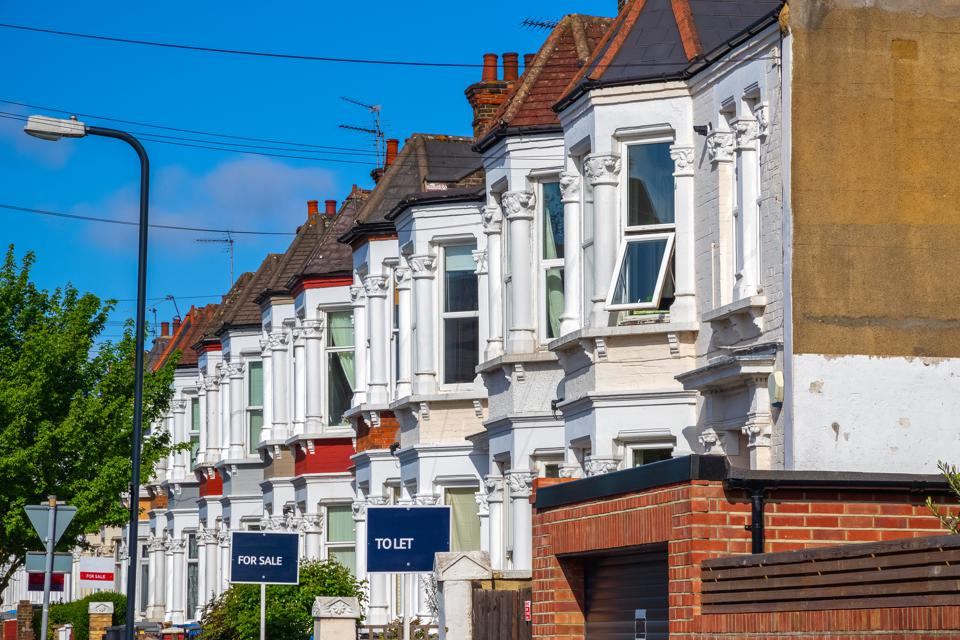 British terraced houses in London with estate agent boards
