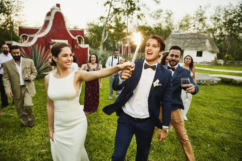 Bride and groom holding sparkler while celebrating during outdoor wedding reception with friends