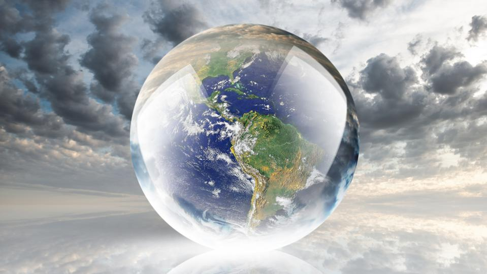 Crystal ball reflecting globe of the earth on clouds background