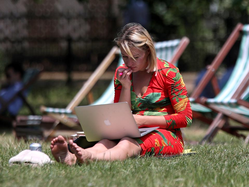 A woman working on a laptop in Green Park, London.