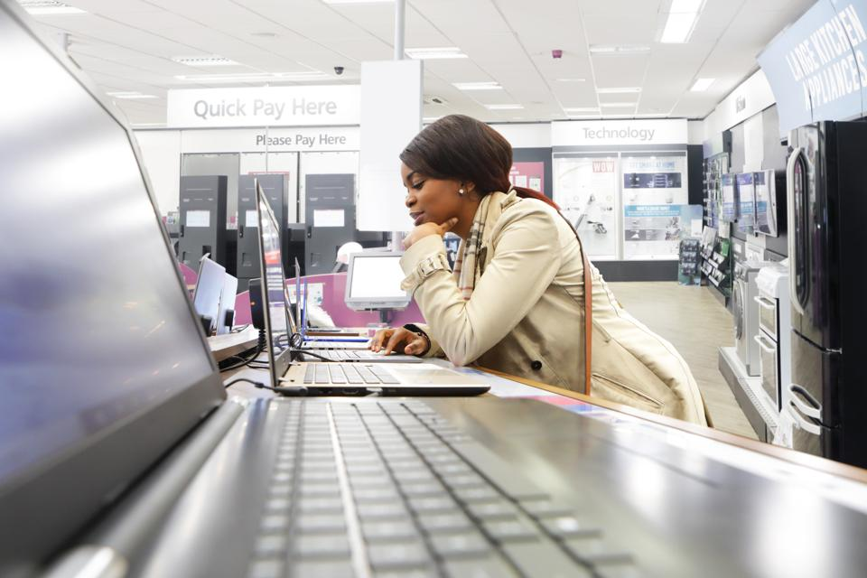 Young woman in shop looking at laptops