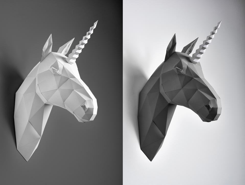 Contrast collage of black and white paper unicorn heads.