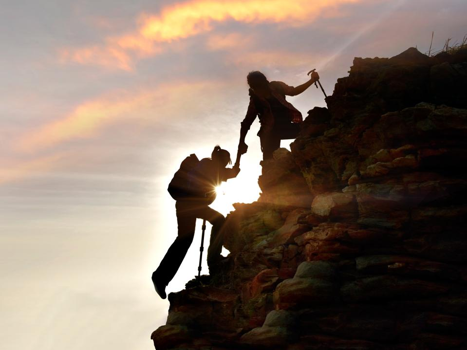Young Asian couple  hikers climbing up  mountain cliff . Climbing ,Helps and Team work concept .