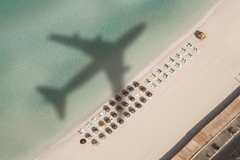 plane flying over beach
