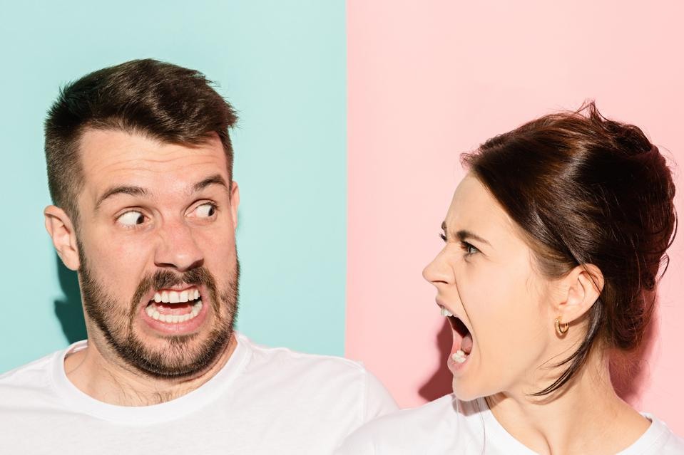 Angry couple fighting and shouting at each other in conflict.