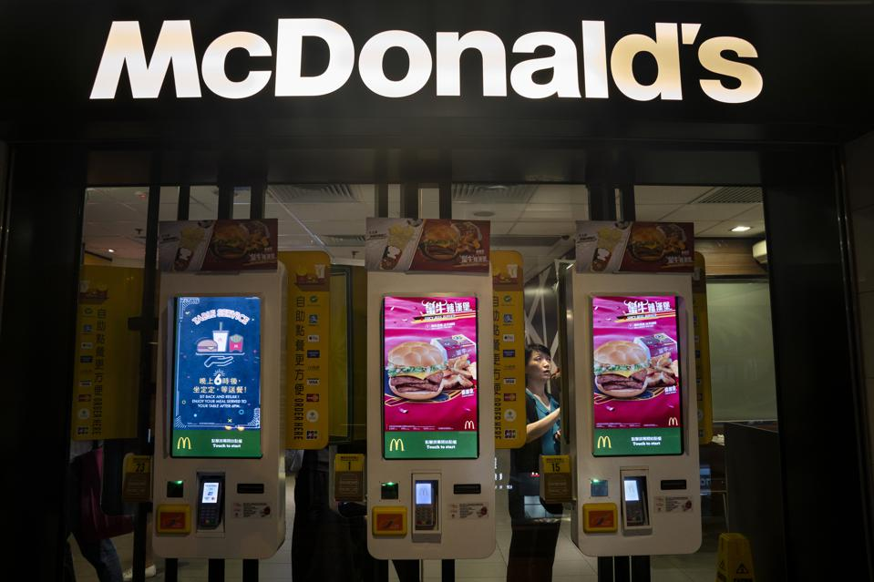 Customers ordering food in automated self-ordering kiosk at...