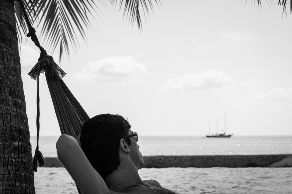Young man with sunglasses resting on a beach hammock while looking at a sailboat on the background in the island of Koh Phangan, Thailand