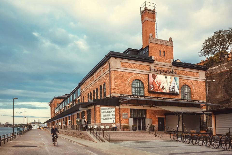 Cyclist driving past bilding of the cultural center Fotografiska with brick walls