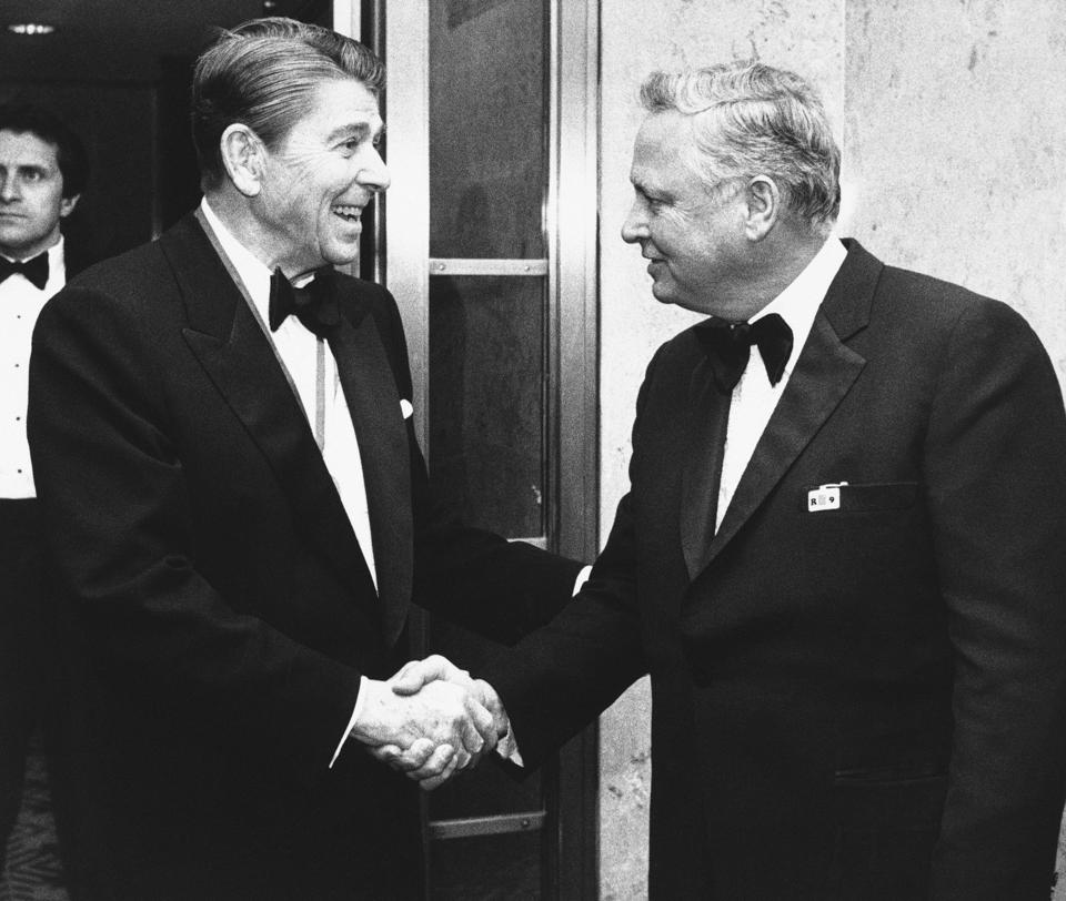 President Ronald Reagan, left, shakes hands with Barron Hilton upon his arrival in Washington D.C. to attend the annual Alfalfa Club dinner on January 26, 1985. (AP Photo/Budd Gray, File)
