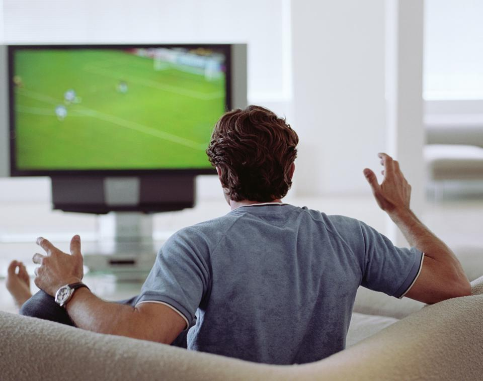 Man watching football on television.