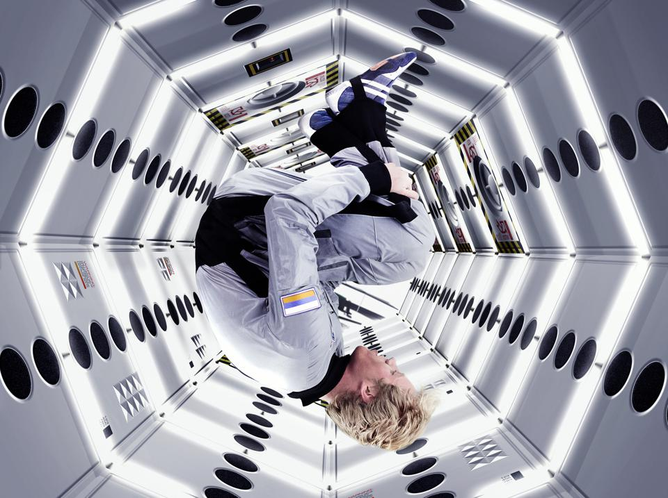 Male astronaut floating upside down in space station (Composite)