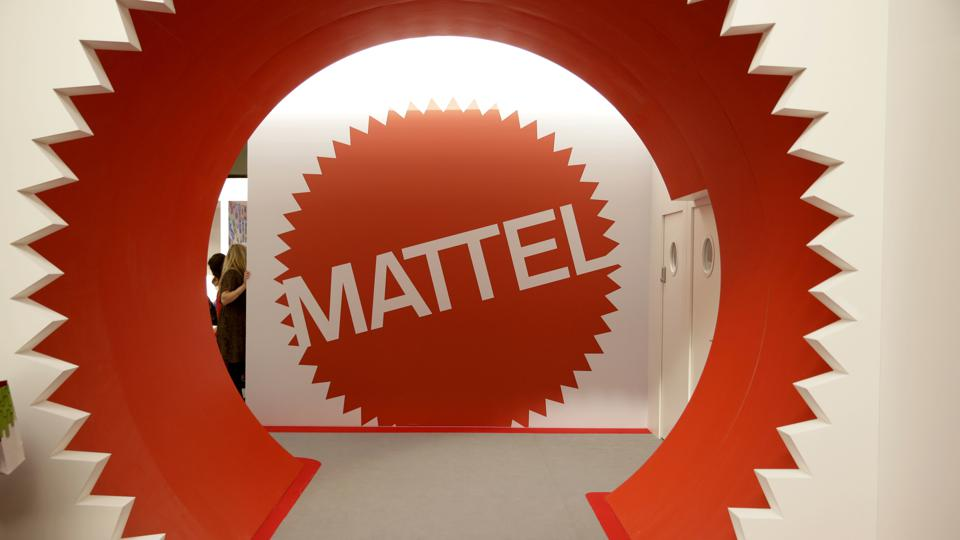 A red and white Mattel logo on display at a Mattel booth at a licensing show.