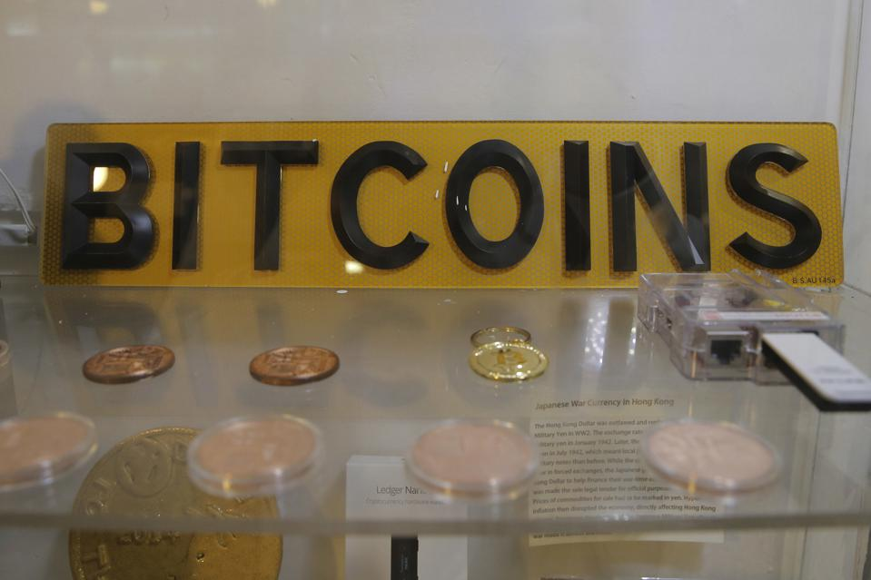 Coins and sign are displayed in Hong Kong. on Dec. 8, 2017.