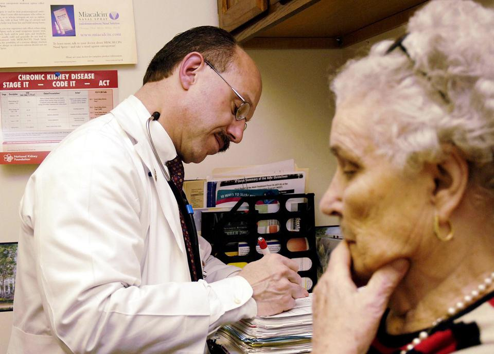 Dr. Joe Vetrano, left, an internist at the Clearfield Professional Group, takes notes after speaking with his patient, Reba Mollica, 84, of Clearfield, Pa., Friday, Nov. 18, 2005, in Clearfield. The most popular spots lately in Vetrano's office are the drawers and cabinets where he keeps free drug samples, which are invaluable to many elderly patients who are deciphering how to use the new Medicare prescription drug card plan for older Americans, or if to use it at all. (AP Photo/Pat Little)