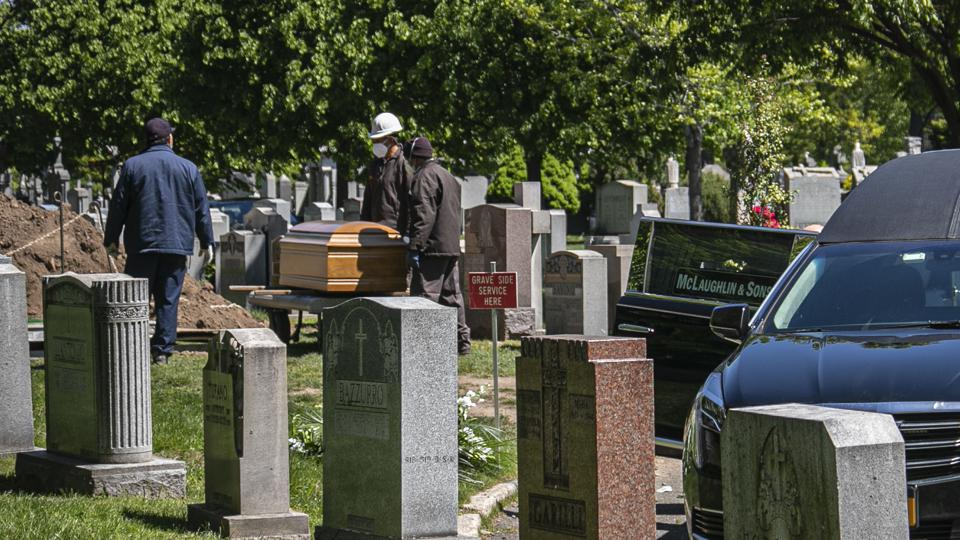 Cemetery workers prepare to bury a casket from McLaughlin & Sons funeral home, without any family present because of coronavirus restrictions, following guidelines from the National Funeral Directors Association (NFDA). (AP Photo/Bebeto Matthews)