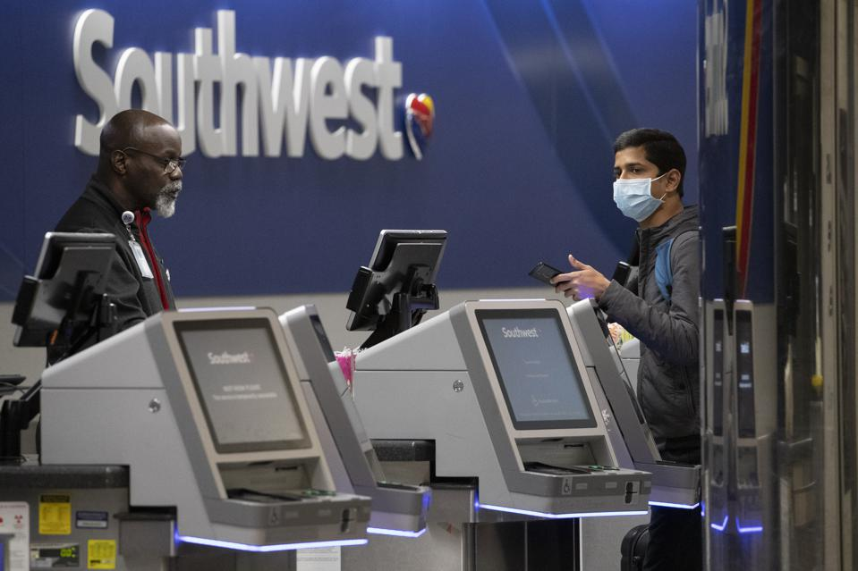 A Southwest Airlines employee assists a passenger wearing a facial mask at New York's LaGuardia Airport Saturday. The Federal Aviation Administration briefly suspended flights to New York City-area airports after a trainee at a regional air traffic control facility on Long Island tested positive for coronavirus. (AP Photo/Mary Altaffer)