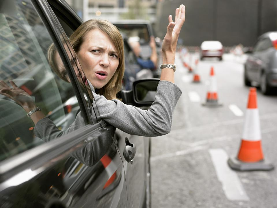 Anoyed Woman Looking Out Her Car Window Gesturing