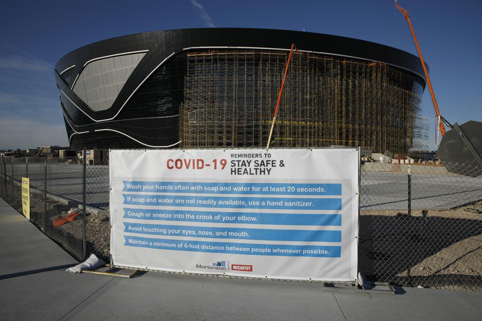A sign gives guidelines for protection from COVID-19 as construction continues at Allegiant Stadium on March 31.