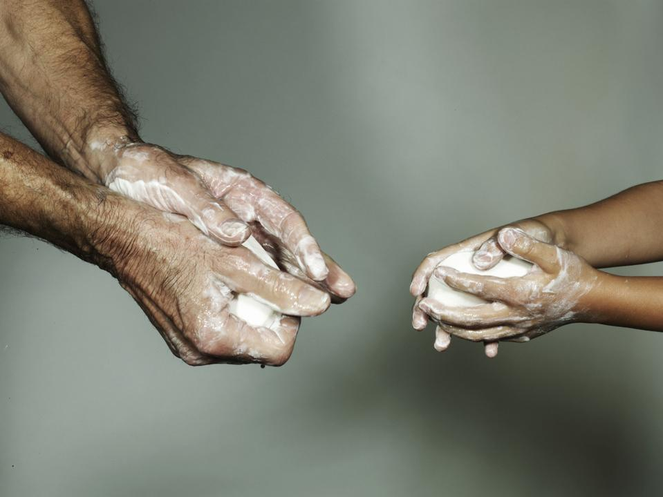 Grandfather and grandson (6-7) washing hands with bar of soap, close-up
