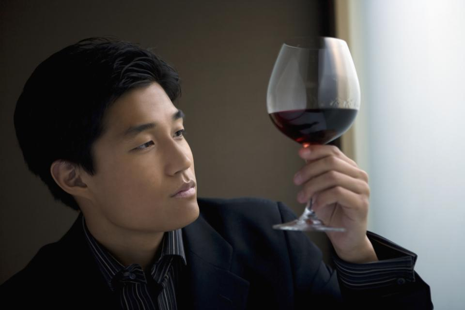 Man observing red wine, indoors