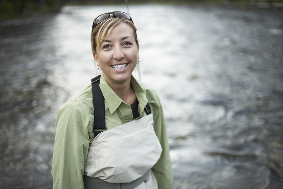 Portrait of mid adult woman in fishing wear standing in river