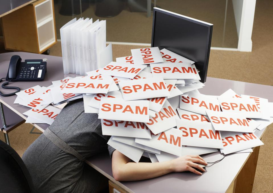 Young businesswoman at her desk covered in a pile of envelopes with SPAM on them